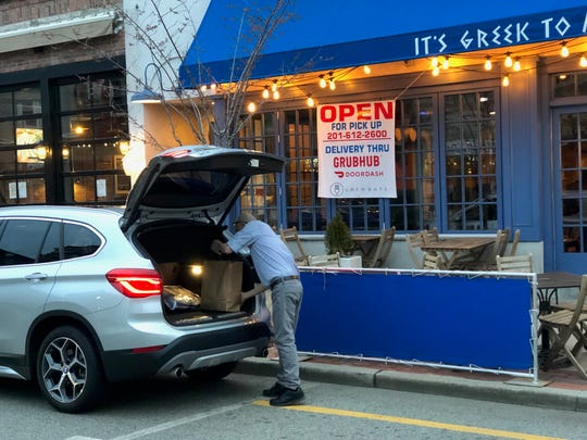 An employee places an order in a trunk outside It's Greek to Me Wednesday, March 18, 2020.