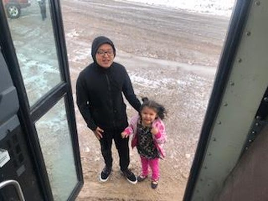 A young girl and her brother greet a Bloomfield school bus on March 19 in the Nageezi area as prepackaged meals were delivered to students in the area.