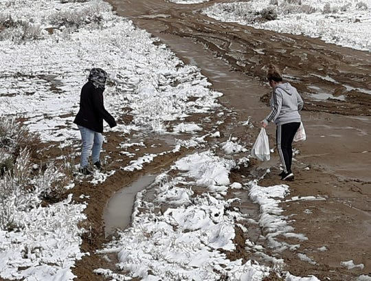 Superintendent Kim Mizell, left, delivers food to a student on a muddy road in the Escrito area on March 19.