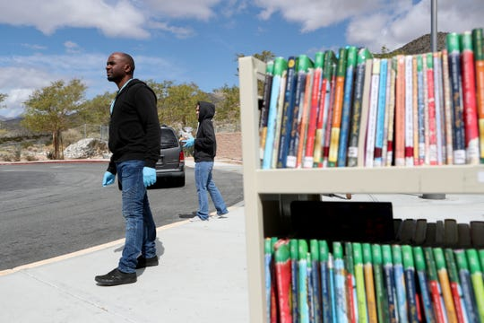Bella Vista Elementary School third-grade teacher Byron Williams helps to give out books, food or paper packets to parents as they drive up outside Bella Vista Elementary School in Desert Hot Springs, Calif., on Thursday, March 19, 2020. The principal gave out district-issued computer laptops to students in grade three and up that hadn't already taken theirs home. Palm Springs Unified School District will soon provide students with weekly lessons.