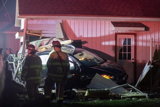Firefighters work at the scene of a two-vehicle crash where a car drove through a garage on the first block of West Granger Street, Thursday, March 19, 2020, in Penn Township.