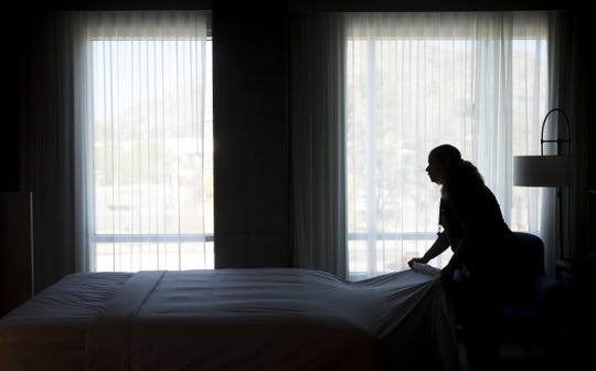 Sally Gerena prepares a bed in a room at Mountain Shadows Resort in Paradise Valley on Feb. 13, 2020.