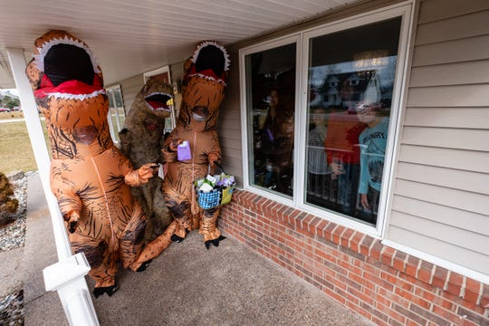 A group of kids smile through the window of a St. Clair home as Renee McCormick, Jaclyn Meldrum and Carrie Bommarito wear T. rex costumes to deliver cookies and other treats Friday, March 20, 2020. The kids stayed inside and the treats were left on the porch to help prevent the spread of coronavirus.