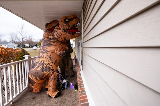 Dressed in T. rex costumes, Renee McCormick, Jaclyn Meldrum and Carrie Bommarito look through the window of a home where they are delivering cookies and other treats to kids Friday, March 20, 2020, in St. Clair. The kids stayed inside and the treats were left on the porch to help prevent the spread of coronavirus.