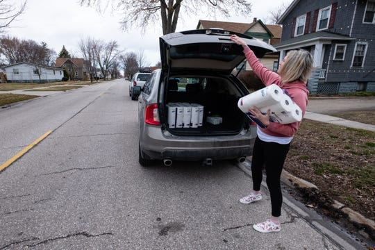 Melissa Mango, from Kimball Township, carries a package of toilet paper to a home Friday, March 20, 2020, in Port Huron. Mango bought extra toilet paper from Sam's Club to distribute to the elderly and homebound who couldn't get their own.