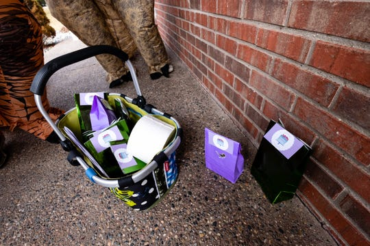 Bags of cookies and other treats are set on the porch of a St. Clair home Friday, March 20, 2020. Bakers from Fondant Grove home bakery baked the goods and delivered them to neighborhood kids while wearing T. rex costumes.