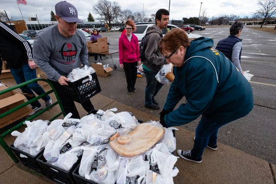 Port Huron football coach Ryan Mullins, left, and teacher Sherri Irish lift packed meals off of a cart Friday, March 20, 2020, at Port Huron High School.