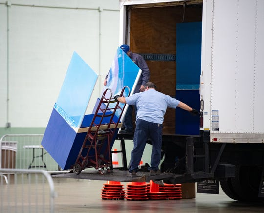 A worker takes barriers made by Plastic Fabricators Inc. into the York Expo Center where they were to be used as protective shields between nurses and patients during COVID-19 testing.