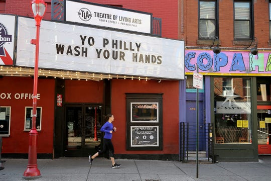 An unidentified jogger cruises by the Theatre of Living Arts with a message on their marque on South Street in Philadelphia, Pa., on March 18, 2020. The message is referencing one of the steps to avoid the coronavirus.  For most people, the new coronavirus causes only mild or moderate symptoms. For some it can cause more severe illness.