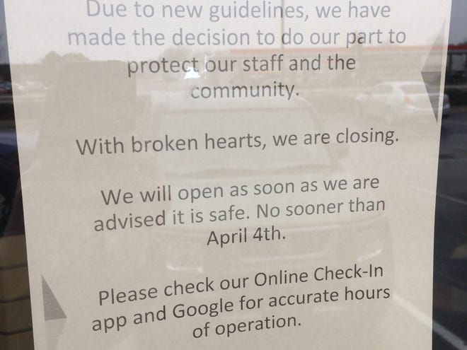 A sign on the door of Richmond's Great Clips explains the store's closure because of the COVID-19 coronavirus pandemic. The store closed before a Wayne County restriction on hair salons was implemented Thursday.