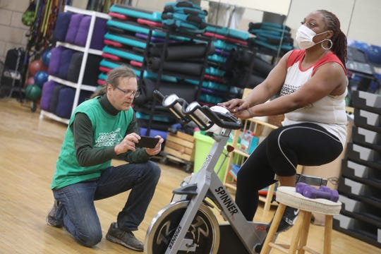 """Karen Rogers, owner of Exercise Express, leads an exercise class starting on a stationary bike as Scott Wagner, left, broadcasts the class live on the Exercise Express Facebook page, at the all-but-empty Danforth Community Center in Rochester Friday, March 20, 2020.  Rogers wanted to make sure those who normally take the class at the center could still have access, and with it """"mental, physical and emotional health,"""" during the coronavirus outbreak."""