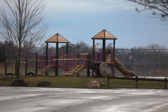 Tape is wrapped around playground equipment in Buckland Park in Brighton on Friday, March 20, 2020.  The town closed its playgrounds to promote social distancing and stop the spread of COVID-19.