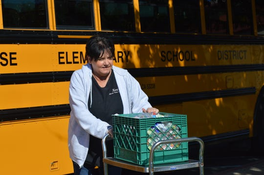 Enterprise School District chef Kori Metz loads a box filled with orange juice, apple juice and milk onto a bus to deliver to families across Redding at Parsons Middle School on March 20, 2020.