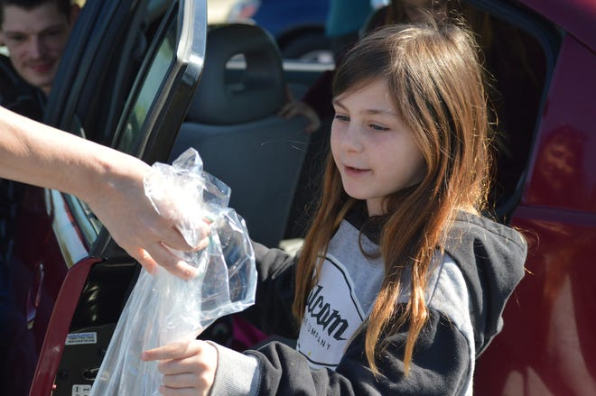 Mistletoe Elementary School student Samantha Knight receives a bag filled with fruits, vegetables, juice, milk and sandwiches from Enterprise School District food service workers at her school on March 20, 2020.