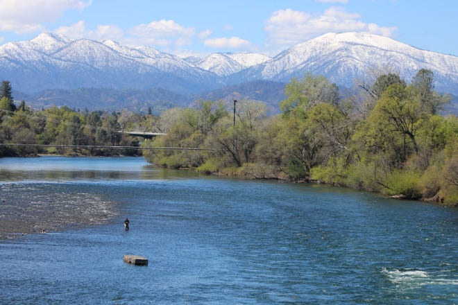 A man fishes in the Sacramento River near Redding's Sundial Bridge on Friday, March 20, 2020, with no problem keeping his social distancing.