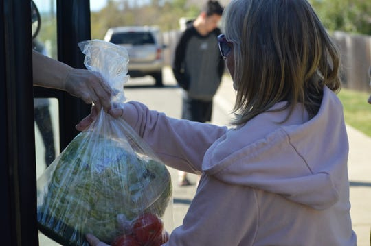Mary Hudson of Redding receives a bag full of produce to make salad for her two grandchildren on Friday, March 20, 2020.