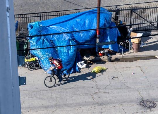 Un hombre que lleva un jersey de los Bulls monta su bicicleta cerca de un par de tiendas de indigentes en Chinatown, el jueves 19 de marzo de 2020.