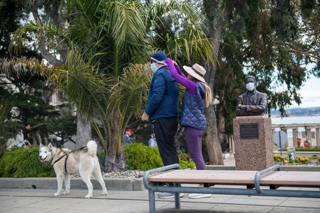 A wife helps her husband put on a facemark during a walk in Monterey on Friday, March 20, 2020.