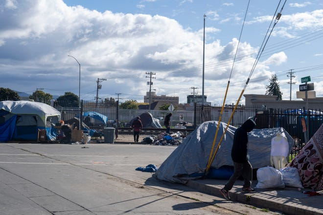 A couple of people walk near the homeless tents in Chinatown on Thursday, March 19, 2020.