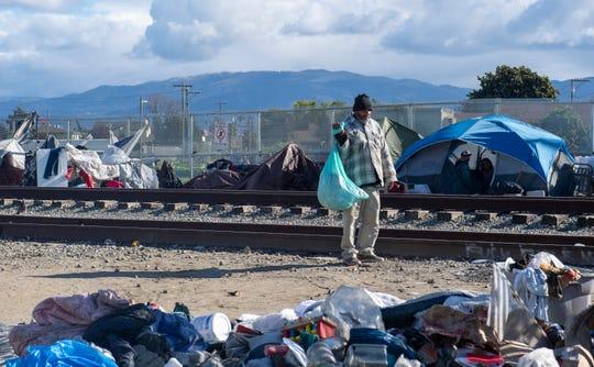 Un hombre carga una bolsa llena de cosas cerca de las vías del tren en Chinatown, el jueves 19 de marzo de 2020.