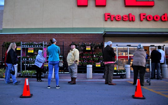 People wait in line to get in to the H-E-B on Sherwood Way on Friday, March 20, 2020.