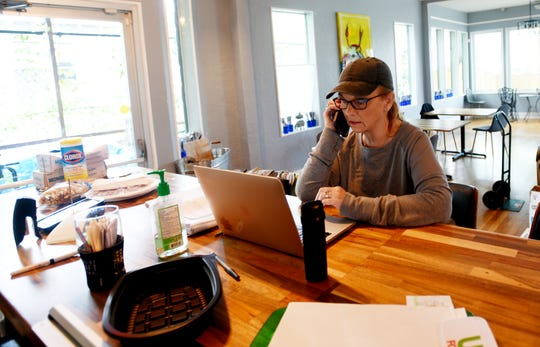 Fat Calf Brasserie operations manager, Bernice 'Mama B' Kovac, talks to employees over the phone. The restaurant will temporarily close until it is safe to open again because of coronavirus.