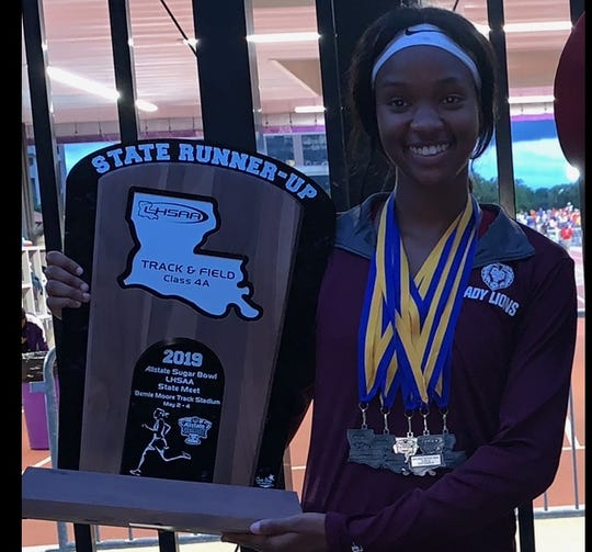 BTW's Alexus Harris holds up the LHSAA Class 4A state runner-up trophy the Lady Lions earned in 2019.