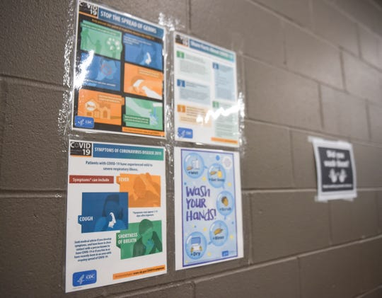 Posters listing the symptoms of the coronavirus are posted on the wall on Thursday, March 19, 2020 at the Bishop Dudley Hospitality House in Sioux Falls.