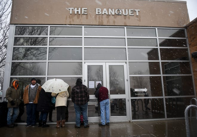 People wait in line in the snow to pick up to go meals on Thursday, March 19, 2020 at the The Banquet in Sioux Falls. In response to the coronavirus, The Banquet closed its dining room and is handing out meals to go.