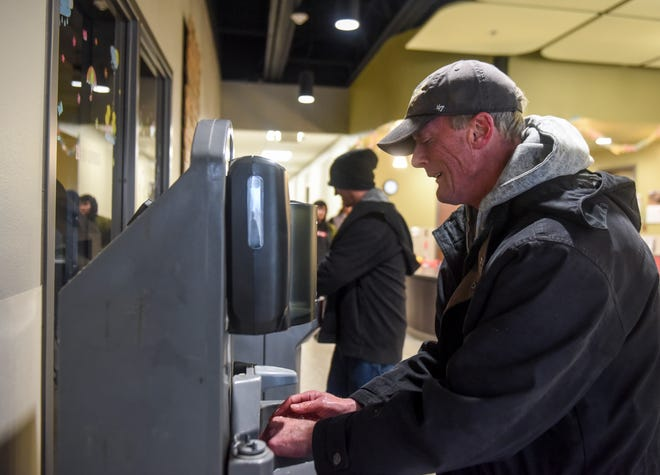 Michael Hanson washes his hands at a makeshift hand wash station on Thursday, March 19, 2020 at the Bishop Dudley Hospitality House in Sioux Falls. The shelter has implemented hand washing stations near the front entrance and is increasing their sanitization in response to the coronavirus.