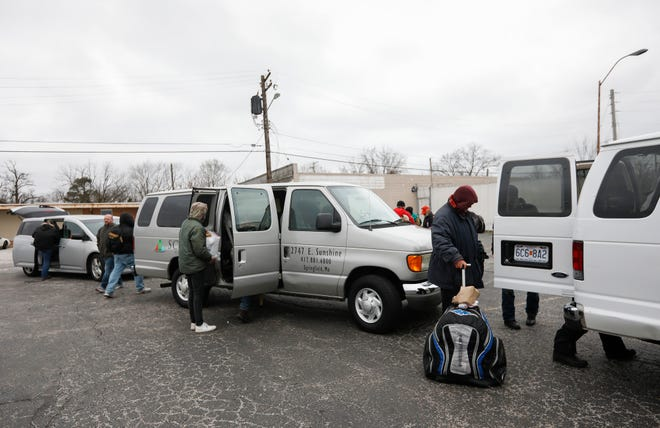 Small groups of homeless men load into vans at the Connecting Grounds before heading to separate venues where 8 of them can sleep overnight on Friday, March 20, 2020. The men's shelters closed due to the coronavirus and with temperatures dropping below freezing on Friday night, area churches and other facilities opened their doors so the men could sleep inside.