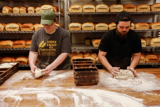 Sarah Conner, left, and Seth Hudspeth shape loaves of Springfield Sourdough bread at Neighbor's Mill Bakery & Cafe's Independence location on Friday, March 20, 2020.