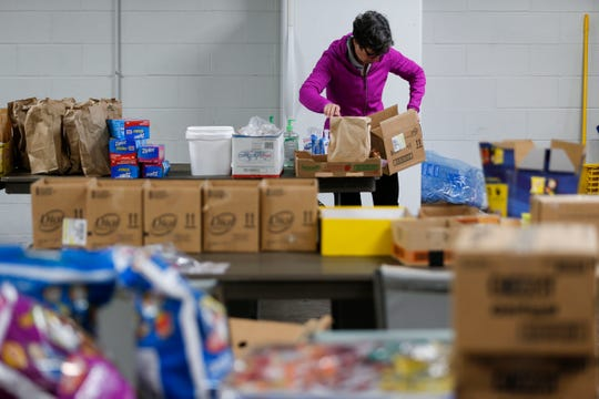 Connecting Grounds volunteer Lola Butcher sorts through donations to put together kits for homeless men that will be sheltering at several churches in small groups as cold weather falls over the Ozarks amid the coronavirus pandemic.