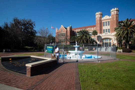 Painters placed a fence surrounding the Westcott fountain on Florida State University's campus, as they repaint the fountain, Wednesday, March 18, 2020.