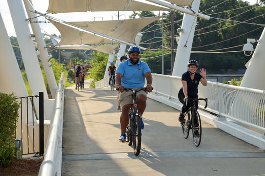 Cyclists on the pedestrian bridge near Cascades Park. Spending time outdoors each day lowers the stress hormone cortisol, which means you enjoy a more positive outlook in general.