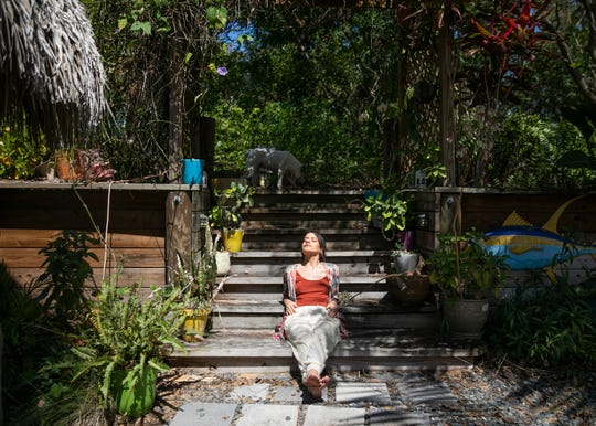 """Zai De Guzman relaxes in her garden with her dog, Lady Bird. """"I've been making it a point to get some sun and fresh air every day or I'll go stir crazy in this house."""""""
