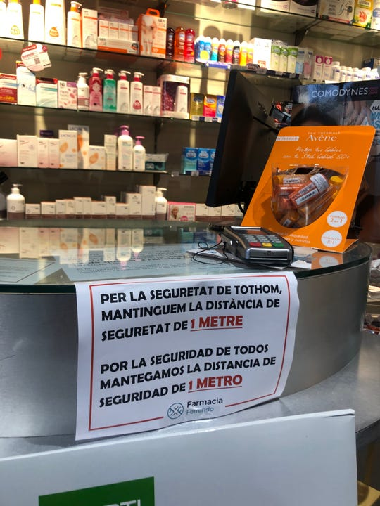 """A sign at a pharmacy in the Barcelona Gothic Quarter warns customers Friday, March 13, 2020: """"For the safety of others, keep a distance of 1 meter."""""""