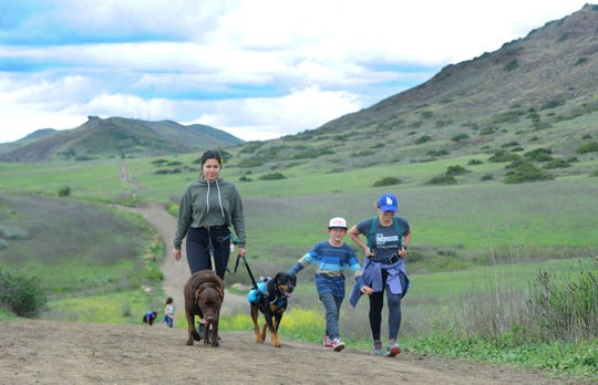 Val Silva, left, walks dogs Duke and Roscoe with Daniella Sosa and Hayden Kelly, 6, all of Simi Valley, returning to the parking lot at Wildwood Regional Park Friday in Thousand Oaks. Hikers kept to their own groups and their distance from others. The latest county order recognizes residents' need to exercise outdoors so long as distance is kept.