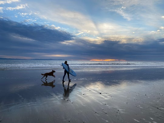 A surfer and her dog enjoy a sunset near Emma Wood State Beach on Feb. 28, 2020.