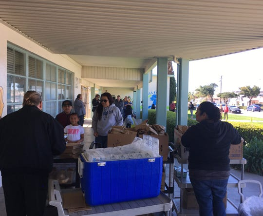 Students and families line up to receive a lunch at Will Rogers School in Ventura on Wednesday. Ventura Unified School District suspended its meal service on Friday.