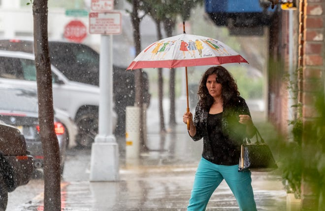 Pedestrians dodge puddles in downtown Visalia in this March 2020 file photo.