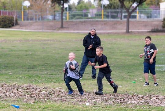 Daniel Hermosillo and Jordan Hermosillo, 8, watch as Nathaniel Hermosillo, 5, runs from Jacob Angulo, 10, at Cherry Avenue Park on Thursday, March 19, 2020.