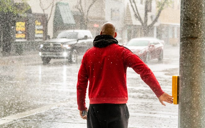 A pedestrian waits for a signal on rain soaked Main Street in Downtown Visalia on Thursday, March 19, 2020.