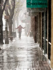 A pedestrian strolls along Main Street during a downpour in Downtown Visalia on Thursday, March 19, 2020.