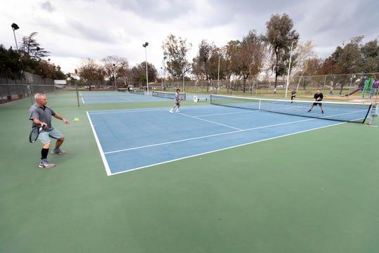Jon Kubar, left, Nolan Yang, Marc Gomez and Travis Gormley play tennis at Plaza Park on Thursday, March 19, 2020.