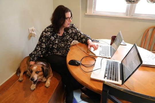 Judy Herbst, director of marketing for Worthy.com, an online auction house, works from home with her dog Denny in Larchmont, NY amid the coronavirus outbreak March 20, 2020.