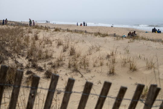 People walk around and relax at Rehoboth Beach Thursday afternoon. Many people still turned out to explore the beach and attractions despite the encouragement for social distancing by state officials.