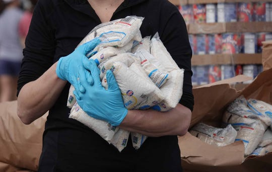 A volunteer for The Food Bank of Delaware holds bags of rice with protective gloves while waiting to give it out at the Dover International Speedway during a Food Bank mobile drive-thru pantry.