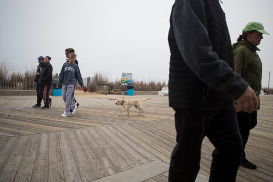 People walk around the boardwalk at Rehoboth Beach Thursday afternoon. Many people still turned out to explore the beach and attractions despite the encouragement for social distancing by state officials.