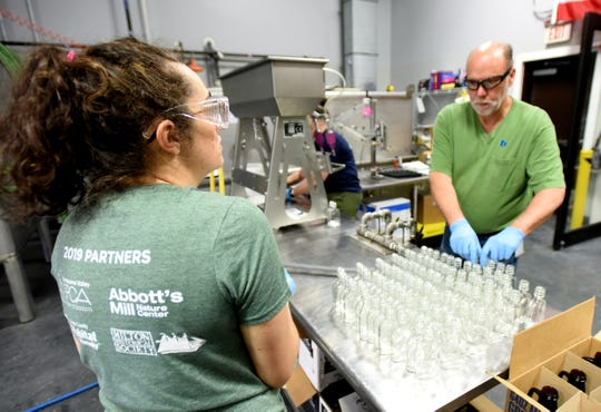 Margaret Egeln and Jeff Mathews fill bottles with Dogfish Head Brewery hand sanitizer.